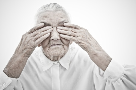 decrepitude: very old woman masking her eyes with her hands Stock Photo