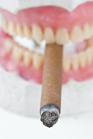 bad hygiene: artificial wax  denture with a   cigarette Stock Photo