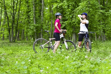two girls having a break during cycling  in the forest photo