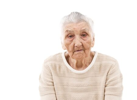 old woman: sad old woman contemplating in front of an isolated background Stock Photo