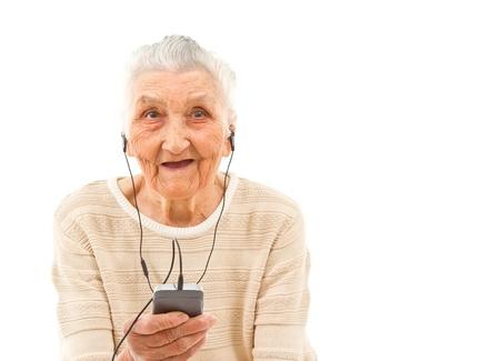 80s adult: se�ora muy vieja aislados en blanco escuchar m�sica en el tel�fono Foto de archivo