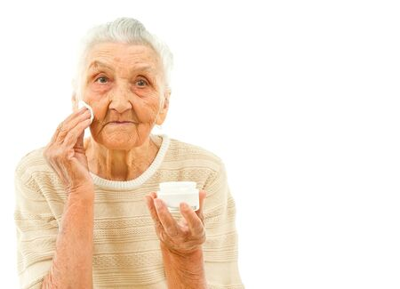 very old lady isolated on white is wiping off her face with a makeup pad photo