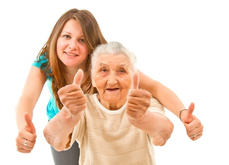young woman with her grandmother showing thumbs up on an isoltad backgroundq photo