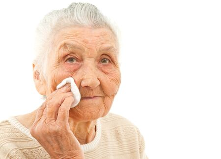 remover: very old lady isolated on white is wiping off her face with a makeup pad