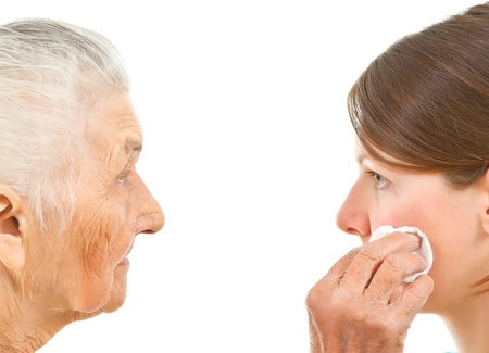 face off: old woman wiping off the face of a young one with a makeup pad