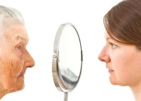 mirar espejo: rostros j�venes y viejos aislados de pie en los dos lados del espejo