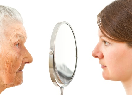 young and old  isolated faces standing on the two sides of the  mirror photo