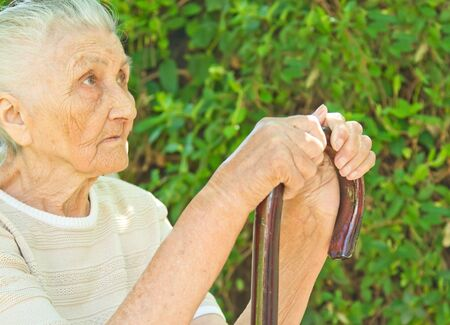 walking stick: very old woman sitting in the park and standing against a walking stick