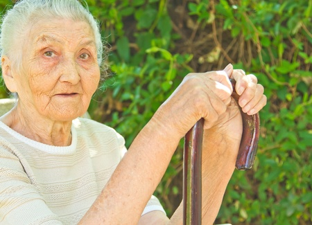 unhealthy thoughts: very old woman sitting in the park and standing against a walking stick