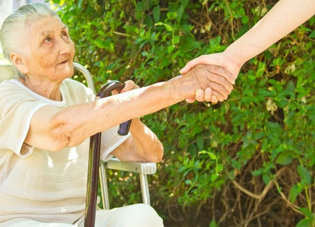 young womans helping hand towards a very old woman sitting in the park Stock Photo