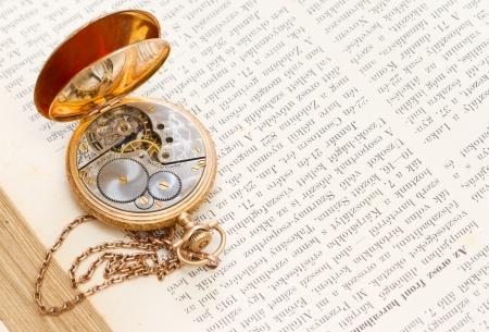vintage gold pocket watch lying on a book photo