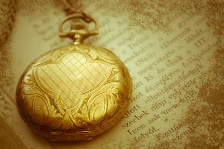 closed vintage  gold pocket watch on a book photo