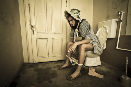 girl in retro countryside costume sittin on the toilet and smoking photo