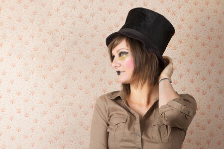 young woman wearing a creative visage and a black top hat photo