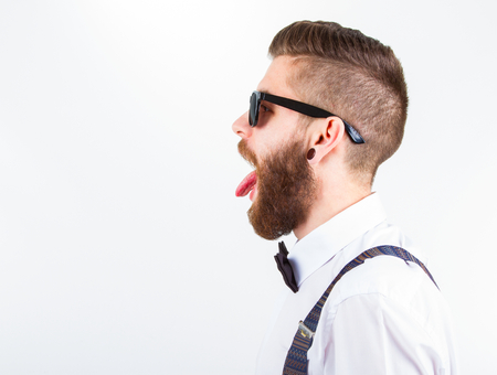 portrait of a young fashionable hipster man who puts out his tongue