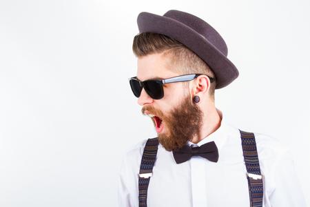 jungen hipster Mann in Hut, Strumpfhalter und Fliege mit offenem Mund isoliert auf weiß