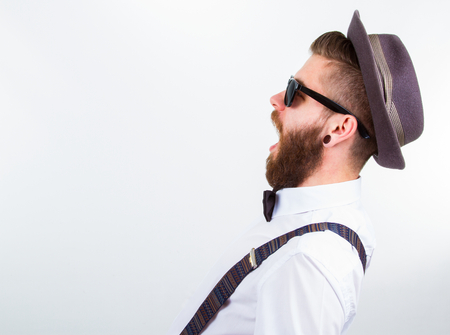 young hipster man wearing  hat , suspenders and bow-tie with open mouth