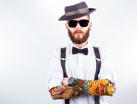 male: young hipster man wearing  hat , suspenders,  bow-tie and a funny tattoo-sleeve