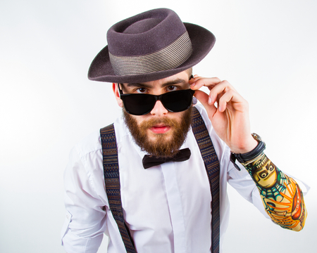 actual: young hipster man wearing  hat , suspenders , a  bow-tie and a funny tattoo-sleeve Stock Photo