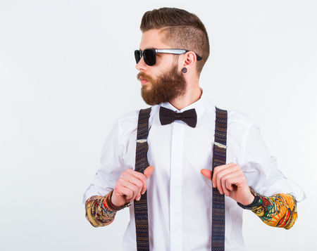 hipster: young hipster man holding his suspenders with   funny tattooed sleeves Stock Photo