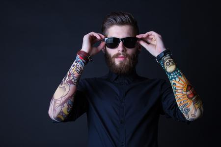 彼の腕のポーズを黒の背景上にカラフルな入れ墨をした身に着けているヒップな男の肖像