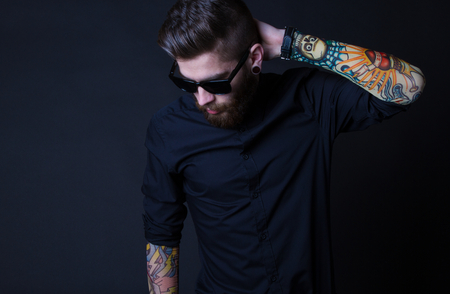 portrait of a hipster man with colourful tattoes posing over a black background