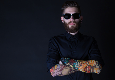 tattooed: portrait of a hipster man with colourful tattoes posing over a black background