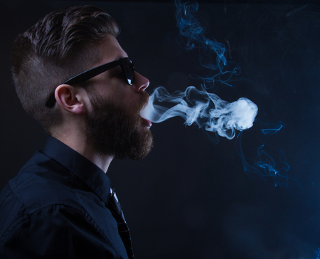 studio portrait of a hipster man smoking with black background