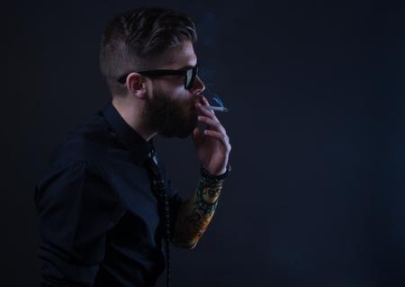 man smoking: studio portrait of a hipster man smoking with black background