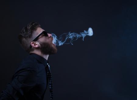 joven fumando: estudio de retrato de un hombre inconformista fumar con el fondo negro