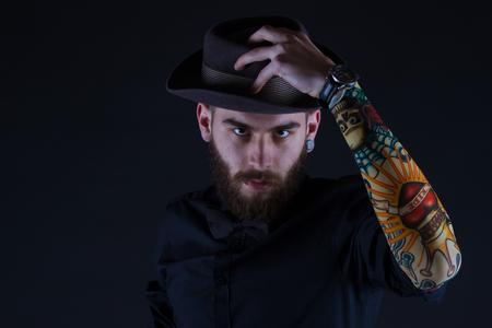 tatouage sexy: portarit studio d'un jeune homme à la mode hippie portant un chapeau élégant, tatoué manches et posant sur un fond noir