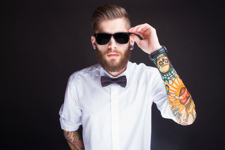 tattoo arm: studio portarit of  ayoung fashionable hipster man in white shirt posing over a black background Stock Photo