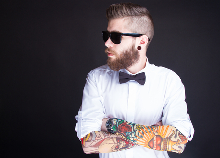 tattooed: studio portarit of  ayoung fashionable hipster man in white shirt posing over a black background Stock Photo
