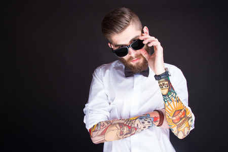 studio portarit of  ayoung fashionable hipster man in white shirt posing over a black background Banque d'images