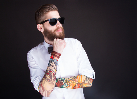 studio portarit of  ayoung fashionable hipster man in white shirt posing over a black background Stock Photo