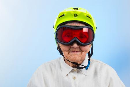 positivism: abuela divertida que lleva un casco de bicicleta amarilla y gafas de esqu� Foto de archivo