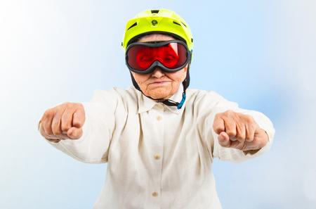 abuela: abuela divertida que lleva un casco de bicicleta amarilla y gafas de esquí Foto de archivo