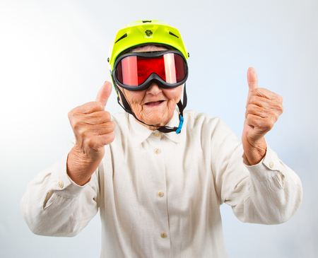 funny grandma wearing a yellow bicycle helmet and ski  goggles and showing thumbs up Archivio Fotografico