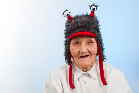 very old lady in funny fur hat with two tentacles