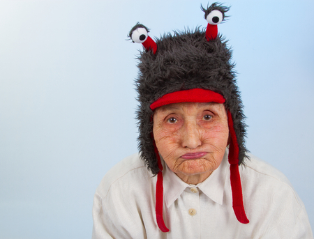 sulky: very old lady in funny fur hat with two tentacles with a bored, sulky expression