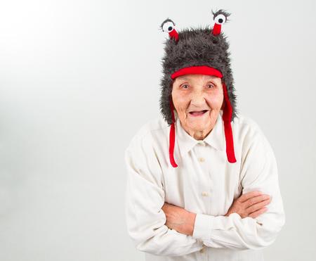 mujeres ancianas: muy anciana en el sombrero divertido de piel con dos tentáculos Foto de archivo