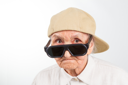 abuela: Retrato de estudio divertido de la abuela llevaba gafas y gorra de béisbol, aislado en blanco