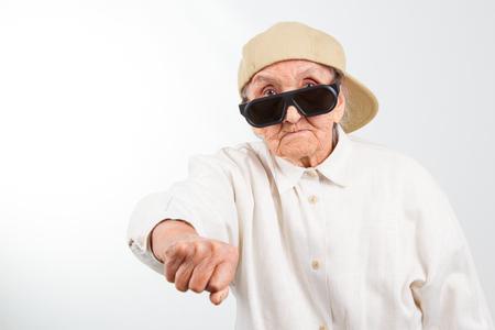 Funny grandmas studio portrait  wearing eyeglasses and baseball cap who kicks with  her fist , isolated on white photo