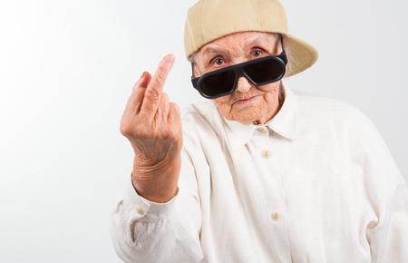 Grappige oma's studio portret dragen brillen en baseball cap, die haar f-vinger geeft, geïsoleerd op wit