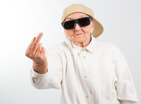 Funny grandmas studio portrait  wearing eyeglasses and baseball cap, who shows her f-finger ,  isolated on white Stock Photo
