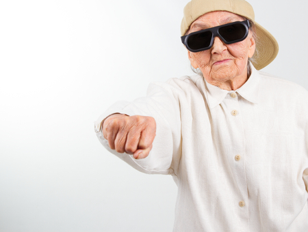 Funny grandmas studio portrait  wearing eyeglasses and baseball cap who kicks with  her fist , isolated on white Stock Photo