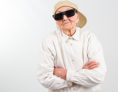 Funny grandma's studio portrait  wearing eyeglasses and baseball cap, who stands for her right,  isolated on white Banque d'images