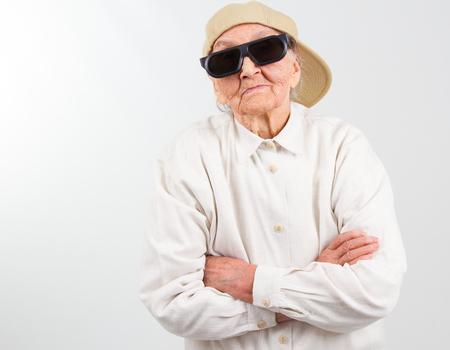 abuela: Retrato divertido de la abuela estudio que llevaba gafas y gorra de béisbol, que se destaca por su derecho, aislado en blanco Foto de archivo