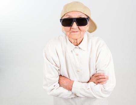 Funny grandma's studio portrait  wearing eyeglasses and baseball cap, isolated on white
