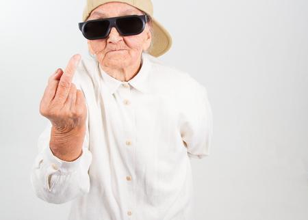 abuela: Retrato divertido de la abuela estudio que llevaba gafas y gorra de b�isbol, que muestra su f-dedo, aislado en blanco